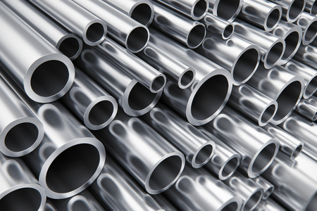 Creative abstract heavy metallurgical industry and industrial manufacturing business production concept: heap of shiny metal steel pipes with selective focus effect Stockfoto