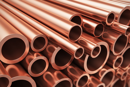 Creative abstract heavy nonferrous metallurgical industry and industrial manufacturing business production concept: heap of shiny metal copper pipes with selective focus effect Imagens