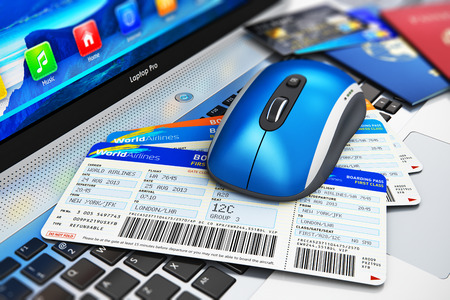 Creative abstract business travel and web online air tickets booking technology internet concept: wireless computer PC mouse and stack of airline boarding pass credit cards and passports on laptop or notebook keyboard with selective focus effect Stock Photo