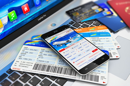 Creative abstract business air travel mobility and communication concept: modern touchscreen smartphone or mobile phone with airline internet web site offering booking or buying airliner tickets online credit cards and passports on laptop or notebook comp