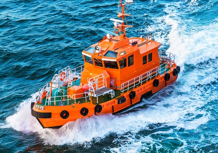 storms: Orange rescue or coast guard patrol boat industrial vessel in blue sea ocean water
