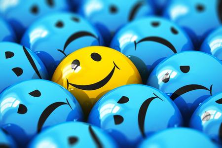 Creatief abstract succes en mensen emotie concept: macro uitzicht op gelukkige gele smiley bal pictogram of knop onder saaie triest blauwe degenen met selectieve focus effect Stockfoto