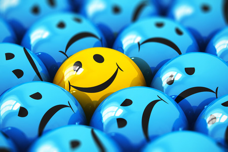 Creative abstract success and people emotion concept: macro view of happy yellow smiley face ball icon or button among dull sad blue ones with selective focus effect