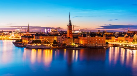 Scenic summer night panorama of the Old Town Gamla Stan architecture pier in Stockholm, Sweden Standard-Bild