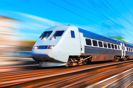 fast train: Railroad travel and railway tourism transportation industrial concept: scenic summer view of modern high speed passenger commuter train on tracks at the station platform with motion blur effect