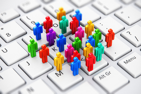 Creative abstract social media, internet communication and business marketing corporate web concept: macro view of group of 3D color people figures on white laptop or notebook computer PC keyboard with selective focus effect Stock Photo