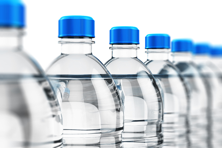 Row of plastic bottles with clear purified drink carbonated water isolated on white background with selective focus effect