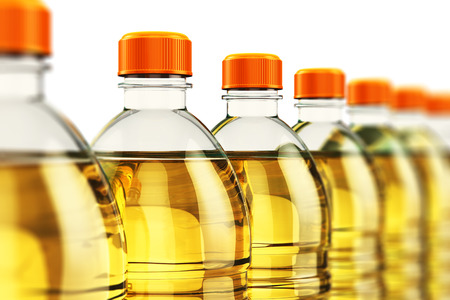 Row of plastic bottles with yellow refined vegetable cooking oil or organic fat isolated on white background with selective focus effect