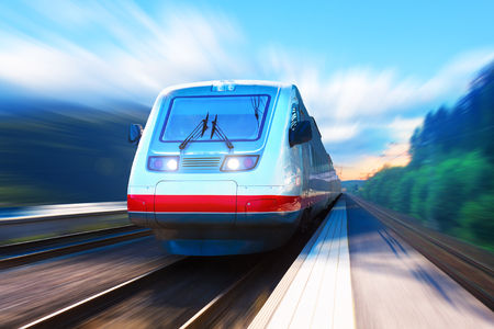 Creative abstract railroad travel and railway tourism transportation industrial concept: scenic summer view of moving modern high speed streamlined passenger commuter train on tracks with motion blur effect Фото со стока
