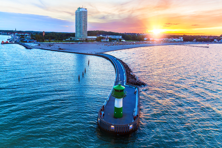 Scenic summer sunset with Baltic sea beach resort and lighthouse pier in Travemunde, Germany