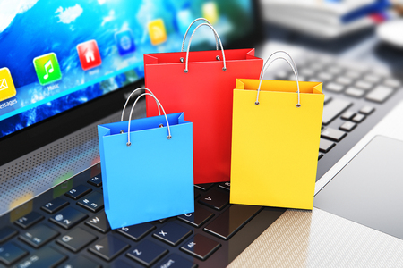 internet sale: Creative abstract commercial internet business retail sale and web online shopping discount offer concept: 3D render illustration of macro view of the group of color paper shopping bags on modern laptop or notebook computer PC keyboard with selective focu