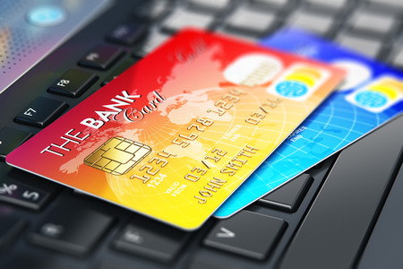paying: Creative abstract internet banking, accounting and online shopping web security business commercial concept: 3D render illustration of macro view of the group of color credit cards on laptop or notebook keyboard with selective focus effect