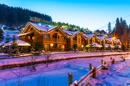 Scenic winter view of mountain ski resort with snowy house cottages with forest and skiing slope in Bukovel, Ukraine