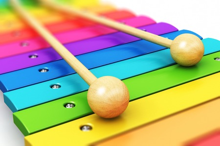 Creative abstract percussion musical instrument and music art creation concept: 3D render illustration of colorful rainbow wooden xylophone with two wood drum sticks isolated on white background with selective focus effect