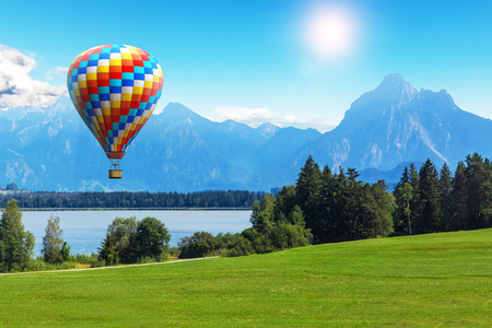 blue summer sky: Scenic summer landscape with colorful hot air balloon flying above Alps mountains, lake and green field or meadow and forest in Bavaria, Germany, Central Europe