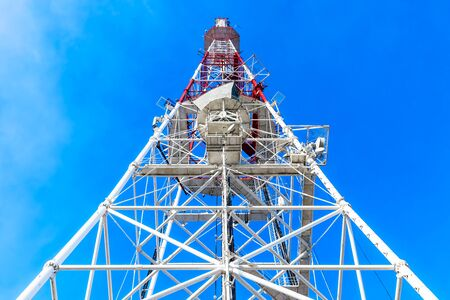communication industry: Creative abstract wireless internet communication, global mobile web connection and television and radio  broadcasting TV industry business concept: high angle view of communication tower with antenna and satellite dish wave transmitter pylon against blue Stock Photo