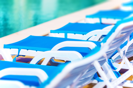 Creative abstract travel, tourism and summer vacation holidays activity concept: macro view of chaise longue beach chairs and swimming pool with blue water in tropical spa resort hotel with selective focus effect