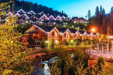 Scenic summer view of winter mountain ski resort with house cottages with forest and skiing slope in Bukovel, Ukraine