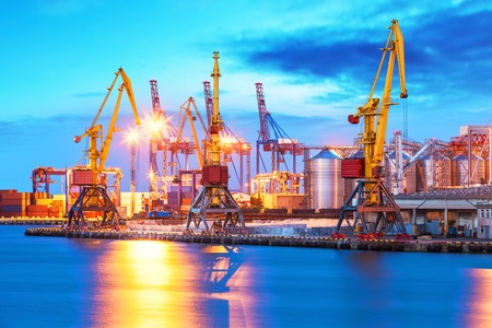 Creative abstract shipping and logistic commercial business industry concept: scenic evening view of the freight sea port with ship cranes and cargo containers