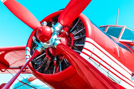 airstrip: red retro propeller engine airplane against blue sky