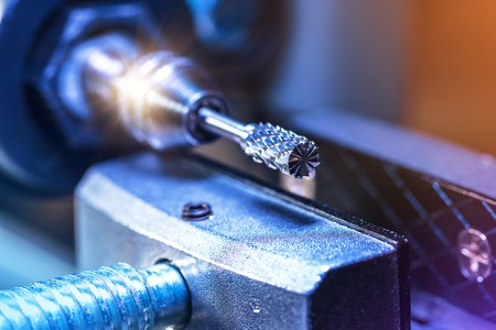 L'industrie lourde abstraite créative, le traitement des métaux et le concept d'entreprise industrielle de fabrication de l'acier: vue macro de l'extrémité de la lame rotative de la machine de découpe CNC avec effet de mise au point sélective Banque d'images