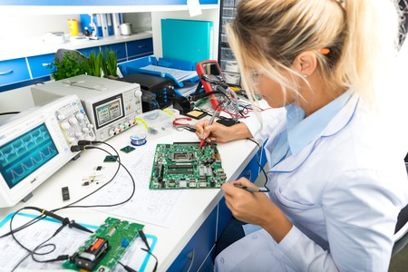 Young attractive female digital electronic engineer testing computer PC motherboard in laboratory