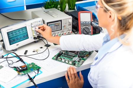 젊은 매력적인 여성 전자 엔지니어 실험실에서 디지털 오실로스코프를 사용 하여