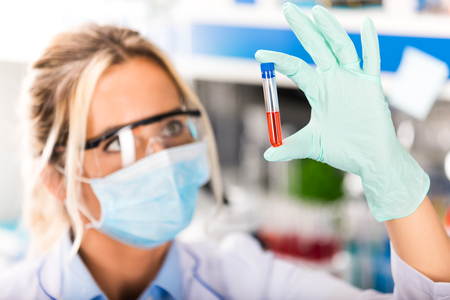 Young attractive female scientist in protective eyeglasses and mask examining test tube with red liquid sample substance probe in the scientific chemical research laboratory Stock Photo