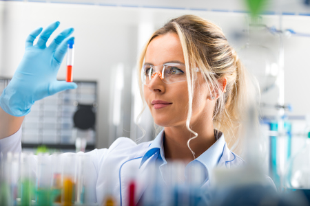 Young attractive female scientist in protective eyeglasses and gloves examining test tube with red liquid sample substance probe in the scientific chemical research laboratory Zdjęcie Seryjne - 85043459