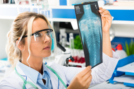 Young attractive female scientist with protective eyeglasses examining X-ray photography film results of the human chest in the scientific hospital clinic medical laboratory