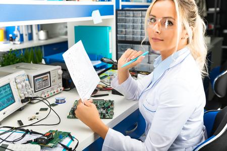 Jonge aantrekkelijke vrouwelijke digitale elektronische ingenieur die elektronische kring in laboratorium controleert Stockfoto