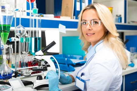 Young attractive woman scientist in protective glasses and gloves researching in the scientific chemical laboratory Stock Photo
