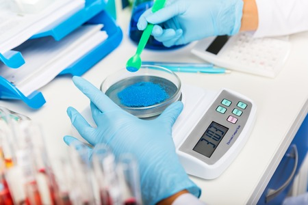 Scientist in gloves measuring weight of blue bulk solid substance in the scientific chemical laboratory