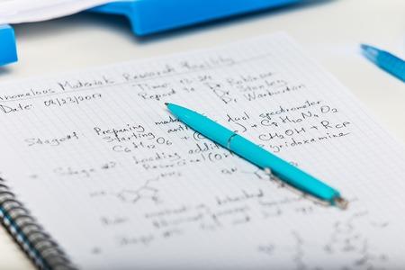 과학적 연구 보고서 및 선택적 포커스 효과 가진 실험실 테이블에 파란색 펜 메모장