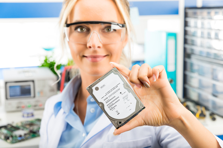 hard disk: Young attractive happy smiling female digital computer electronic engineer with protective sunglasses holding 2.5 inch laptop or notebook HDD hard disk drive in hand in the laboratory