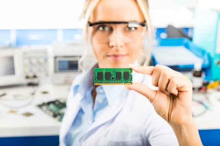 Young attractive smiling female digital computer electronic engineer with protective sunglasses holding laptop or notebook computer DRAM memory module in hand in the laboratory Stock Photo