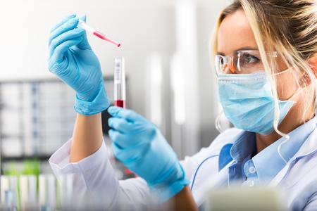 Joven atractivo concentrado científico femenino en anteojos protectores, máscara y guantes cayendo una sustancia líquida roja en el tubo de ensayo con una pipeta en el laboratorio químico científico