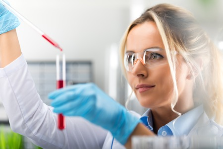 Young attractive female scientist in protective glasses and gloves dropping a red liquid substance into the test tube with a long glass pipette in the scientific chemical laboratory Stock Photo