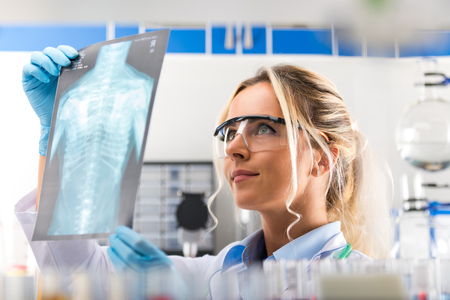 Young attractive female scientist with protective eyeglasses examiming X-ray photography film results of the human chest in the scientific hospital clinic medical laboratory Stock Photo