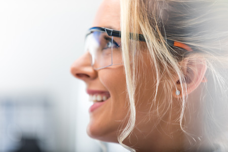 Closeup macro side view profile portrait of the young attractive happy smiling woman in protective eyeglasses Stock Photo
