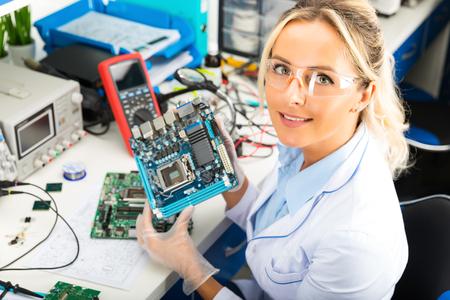 젊은 매력적인 미소 여성 디지털 전자 엔지니어 실험실에서 컴퓨터에 손에 들고 컴퓨터 마더 보드