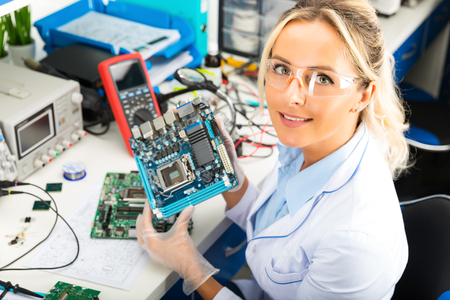 Young attractive smiling female digital electronic engineer holding computer PC motherboard in hands in the laboratory