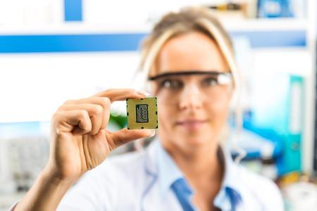 Jonge aantrekkelijke glimlachende vrouwelijke digitale computer elektronische ingenieur met beschermende zonnebril die de bewerkercpu-spaander van PC van de computer in hand in het laboratorium houden Stockfoto