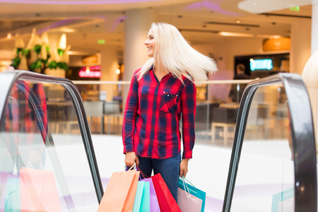 consumerism: Young blonde smiling attractive woman with long hair with a lot of color shopping bags on escalator in the fashion store