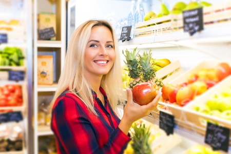 Young smiling attractive woman holding a fresh red apple in her hand at the food store