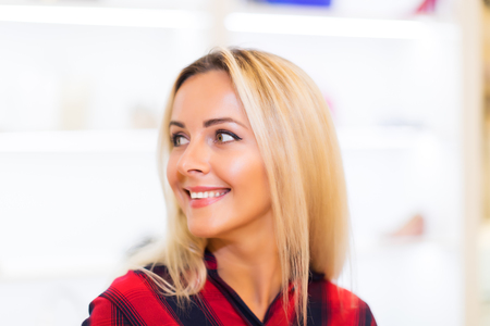 Head and shoulders portrait of young attractive smiling woman with long blonde hair looking to the left side in the fashion wear garments apparel store Stock Photo