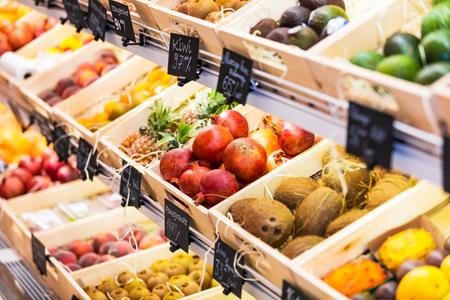 Auswahl an frischen exotischen Früchten im Supermarkt - Ananas, Kokosnüsse, Avocado, Kiwi, Orangen und andere