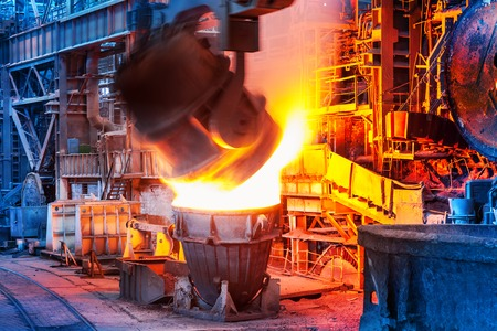 Pouring of liquid metal in open hearth workshop of the heavy industry metallurgical plant