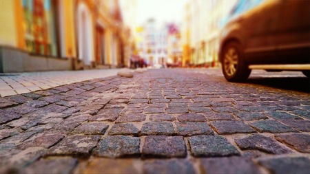 Creative abstract urban architecture retro background: old town street with stone pavement, blurred cars and pedestrians in vintage colors with selective focus effect