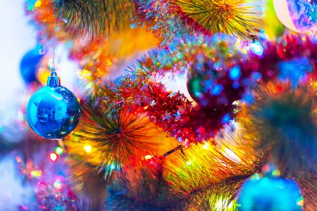 Creative abstract Christmas, Xmas and Mew Year winter holidays celebration concept: macro view of colorful decorated Christmas Tree with shiny metallic balls and color electric garland lights